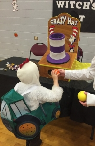 Child in chicken tractor costume throwing balls into tall striped hat carnival game