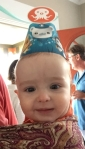Toddler riding in ring sling wearing an Octonauts party hat