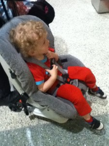Toddler riding in car seat on travel cart wheels in airport next to suitcase