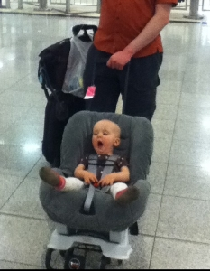 Infant riding in car seat on wheeled travel cart Britax through airport