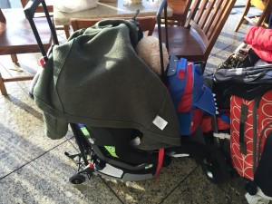 Car seat attached to travel cart hauling other luggage