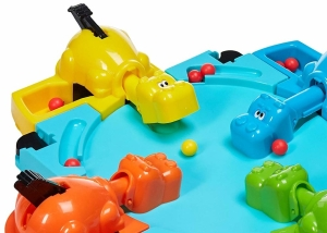 Hungry yellow hippo eating golden marble in table top game