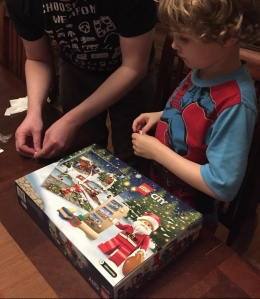 Adult helping child assemble Legos from City advent calendar