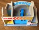 Melissa and Doug Parking Garage Service Station wooden toy set with blue car parked on top deck