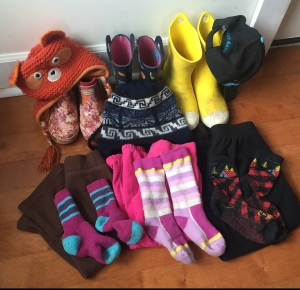 Winter beach wear for three kids including boots, hats, pants, and socks