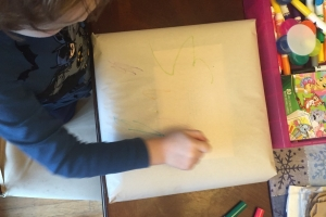 Preschooler decorating gift wrapped in packing paper