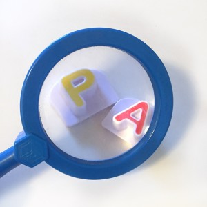 Blue kids magnifying glass enlarging yellow P and red A letters