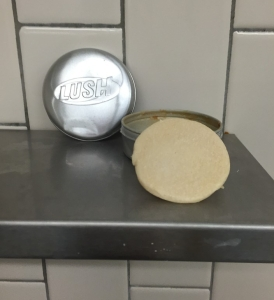 Lush solid shampoo in Godiva scent sitting on shower shelf propped up on tin