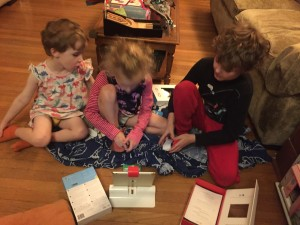 Three kids gathered around Osmo Coding with Awbie on the floor