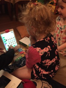 Kids playing Osmo Coding Awbie on living room floor