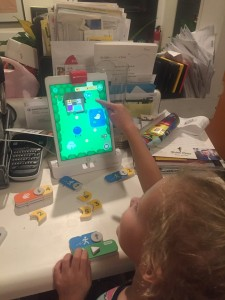 Child manipulating screen in Osmo's Coding with Awbie game
