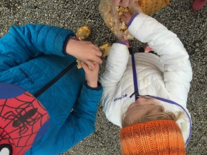 Boys blue and girls white and purple Columbia Powder Lite puffer jackets on kids eating popcorn outside