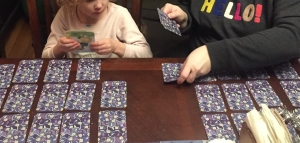 Girl child playing eeBoo Fairy Queen card matching game on table with adult