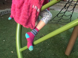 Child climbing play structure in winter coat and too short pants
