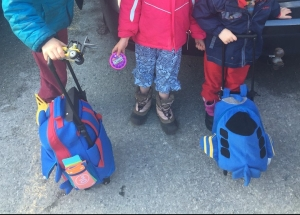 Three kids with rolling backpack suitcases wearing snow boots for travel