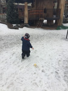 Child in snow clothes and boots walking through snow to playground