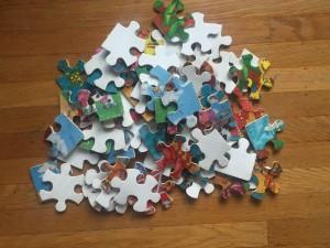 Pile of fuzzy puzzle pieces on hardwood floor