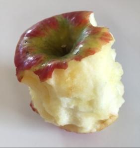 Half eaten red apple turning slightly brown