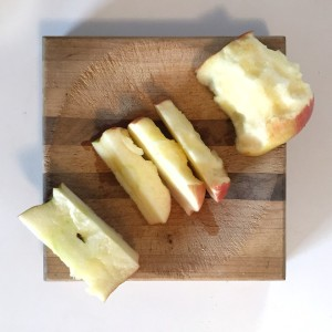 Slicing half eaten apple on cutting board with core