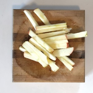 Pile of apple fries sliced rectangular sticks on cutting board