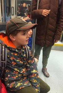 Child wearing Hatley raincoat cars print orange lining on public transportation train