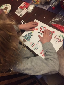Child creating working making melty bead Perla christmas ornaments decorations with patterns