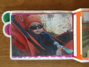 Infant in stroller picture inserted into baby photo book album safe for infants drool proof