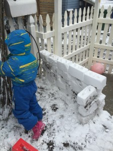 Kid standing next to fort wall built from snow block mold