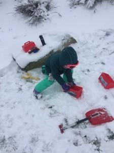 Child filling snow block mold in snow park