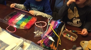 Kids making valentines out of pipe cleaners chenille stems and plastic pony beads