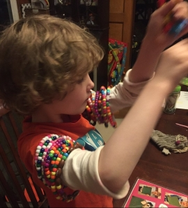 Child making bracelets from plastic pony beads and pipe cleaners