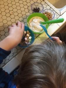 Child adding topppings to bowl of yogurt