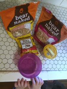 Empty bowl on counter with small child hands, tollhouse chocolate chips, and bear naked granola, tillamook yogurt