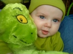 Infant in green hat and green shirt with green Grinch stuffed animal toy
