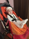 Baby infant in easter outfit riding in orange Bugaboo Frog luxury stroller expensive brand