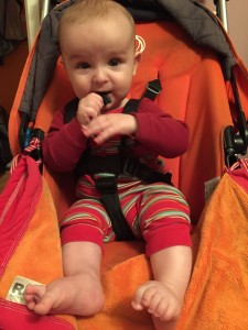 Infant chewing on straps of Bugaboo Frog stroller in orange with RoSK all weather blanket