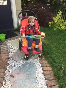 Preschooler in sunglasses riding in Bugaboo Frog stroller on gravel path