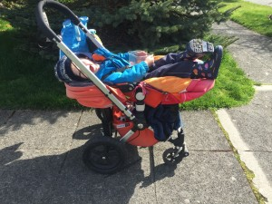 Child reclined in Bugaboo Frog stroller outside in sunshine