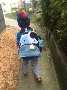 Child walking down sidewalk wearing Skip Hop cow design little kids toddler backpack with skip hop water bottle in side mesh pocket