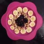 Kid snacks healthy fruit dried fruit nuts arranged on bright pink flower plate