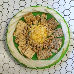 Kids snacks of sliced pears, crackers, cashews, and shredded cheese arranged on bright green plate