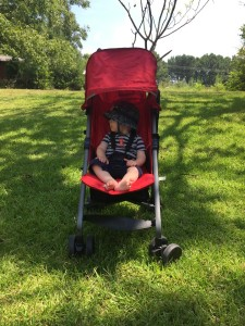 Infant riding in red Joovy Ultralight umbrella stroller parked on the grass
