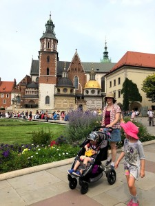 Mom, child walking, and preschooler riding in BOB motion stroller on sidewalk in front of lawn and castle old town towers in Krakow