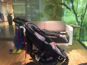 Empty stroller with bags handing off back handle with kid passed out on sofa in background
