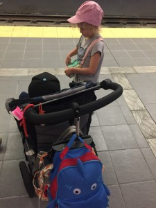 Kid standing next to child in stroller loaded down with bags on train platform