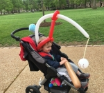 Two and a half year old child riding in BOB motiong stroller with balloon baseball bat and baseball to swing at