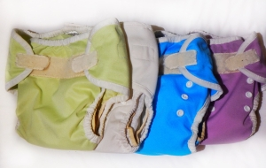 Thirsties cloth diapers covers with inserts stacked on changing table