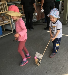Two small kids walking wooden duck push toy on stick with pink head in outdoor market