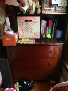 Child's dresser with shelving on top filled with stuff overflowing