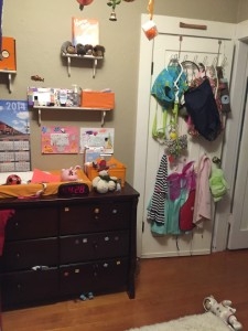 Dresser set up for changing diapers with open shelving above
